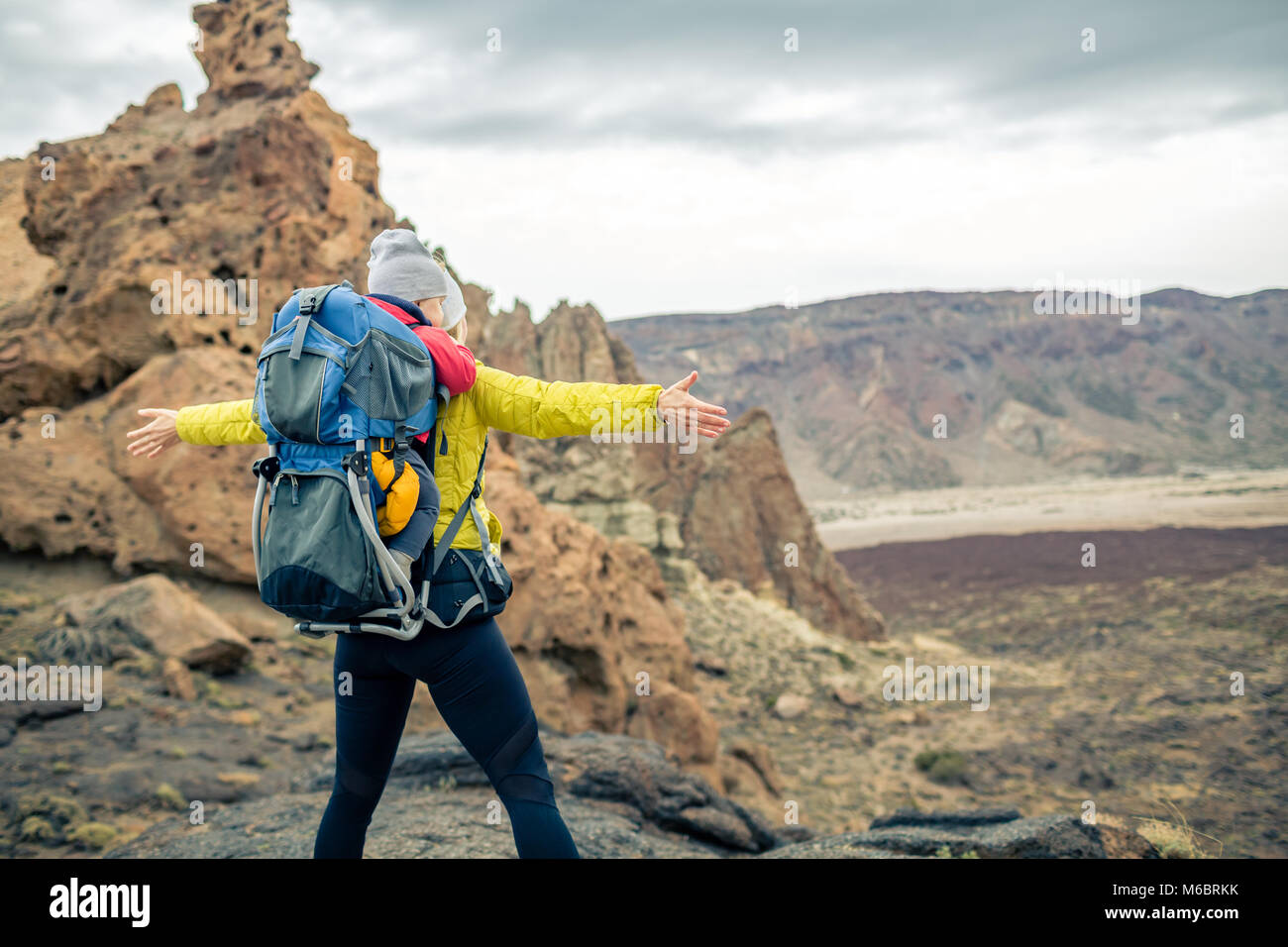 Super mom with baby boy travelling in backpack. Hiking adventure with child on autumn family trip in mountains. - Stock Image