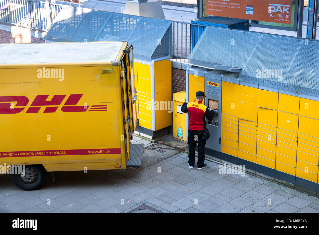 Germany, Cologne, a DHL parcel service driver supplies a Packstation in the district Deutz.  Deutschland, Koeln, - Stock Image