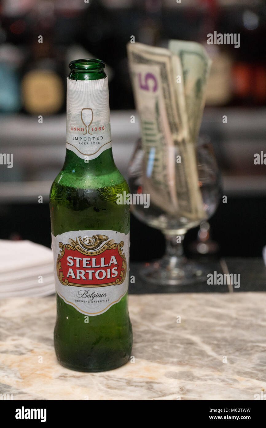 New York, Circa 2018: Stella Artois beer bottle on restaurant bar counter top. Alcohol served to customers by bartender. - Stock Image