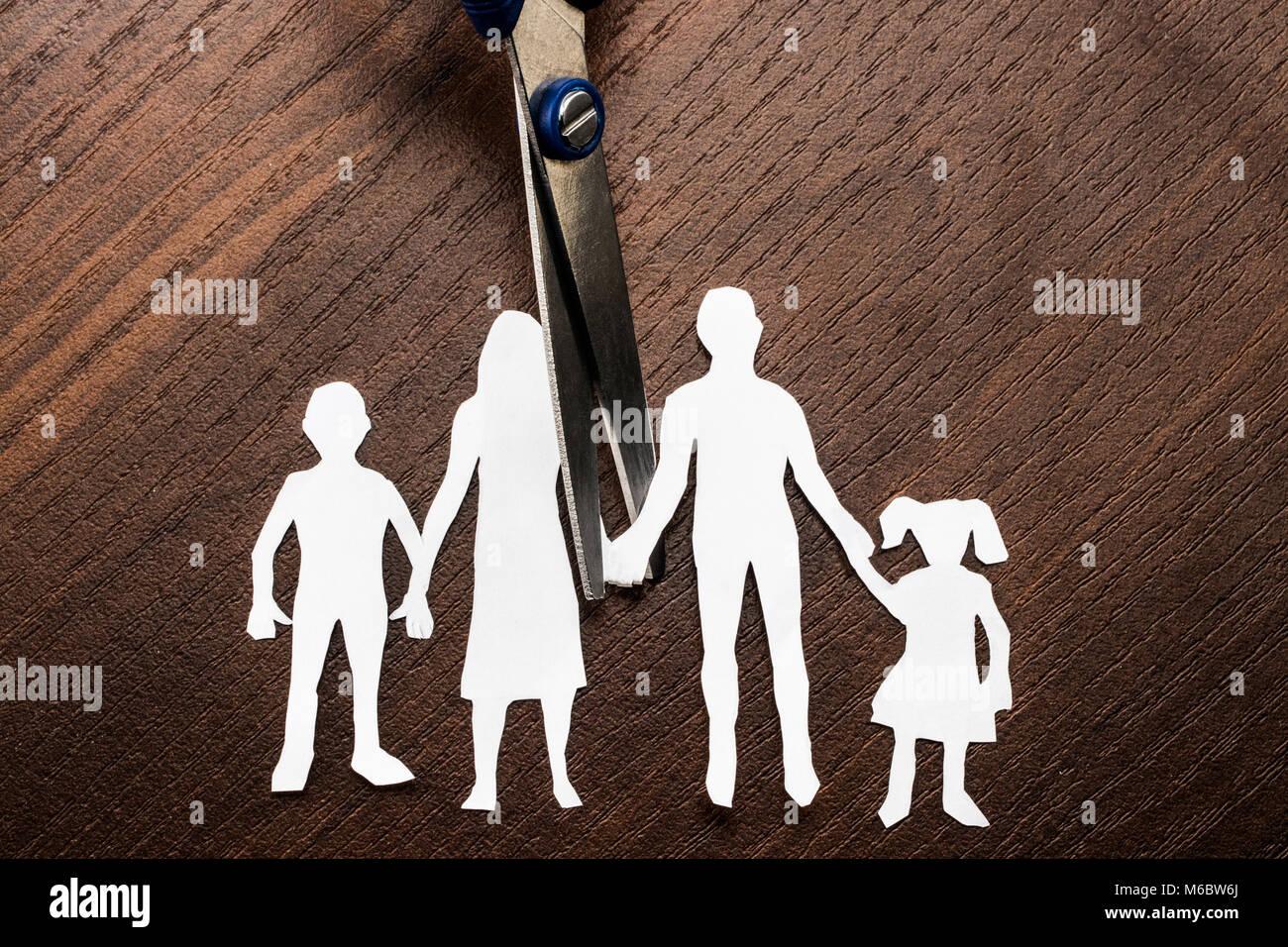 Divorce and child custody scissors cutting family apart. - Stock Image