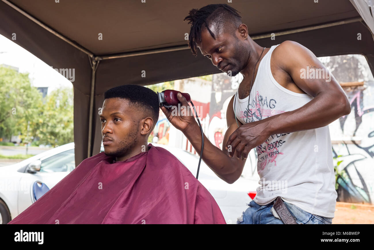 Man having haircut in an informal barber shop in Johannesburg. - Stock Image