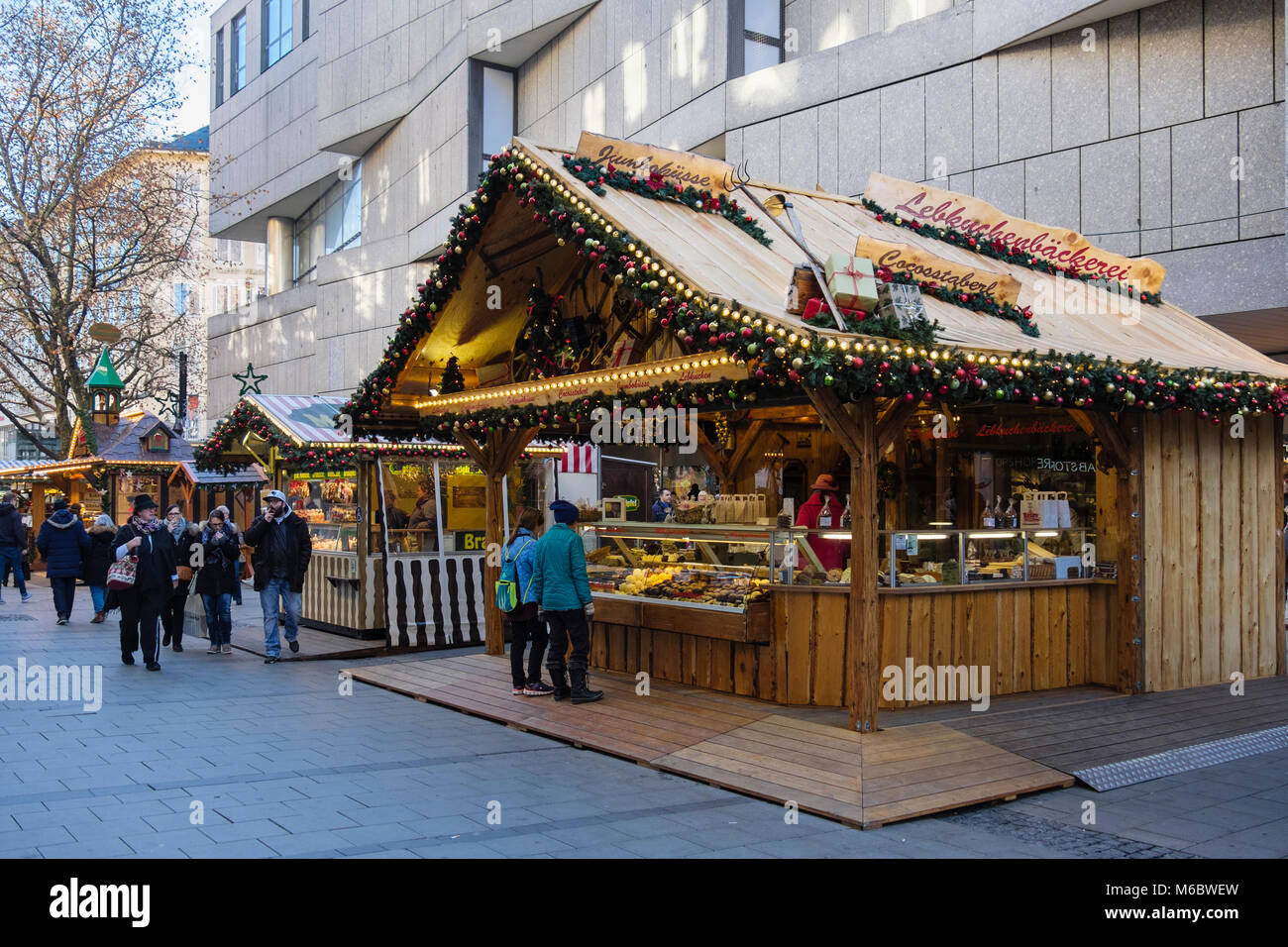 Shoppers and Christmas market food stalls in city centre pedestrianised street. Munich, Bavaria, Germany, Europe - Stock Image