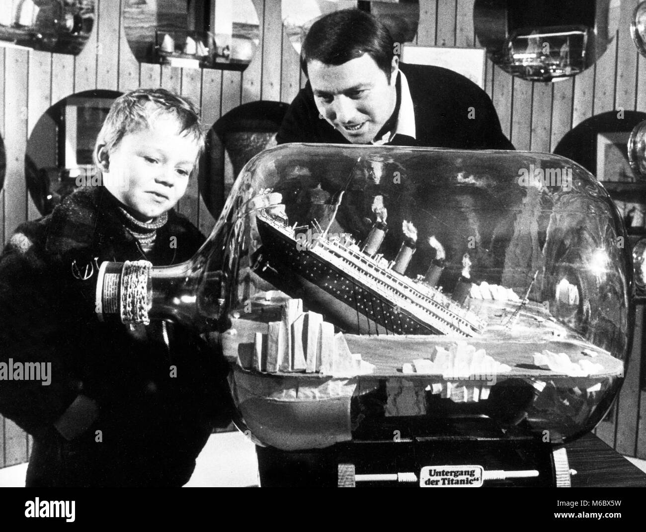 A model of the sinking liner Titanic - wrecked by an iceberg in 1912 - enthrals a young visitor at the Bottle Ship - Stock Image