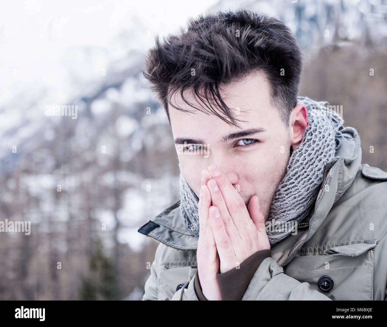 Young man posing at camera in snows - Stock Image
