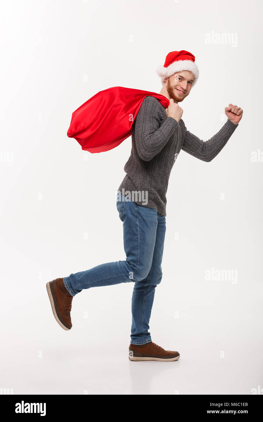 Christmas concept - Young confident beard man running and holding red big santa bag with a lot of present inside. - Stock Image
