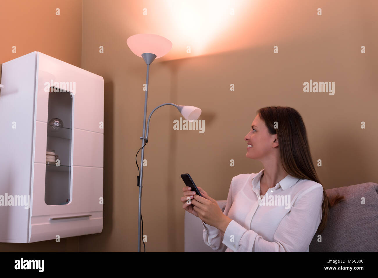 Happy Smiling Woman Controlling Electric Lamp With Mobile Phone At Home - Stock Image