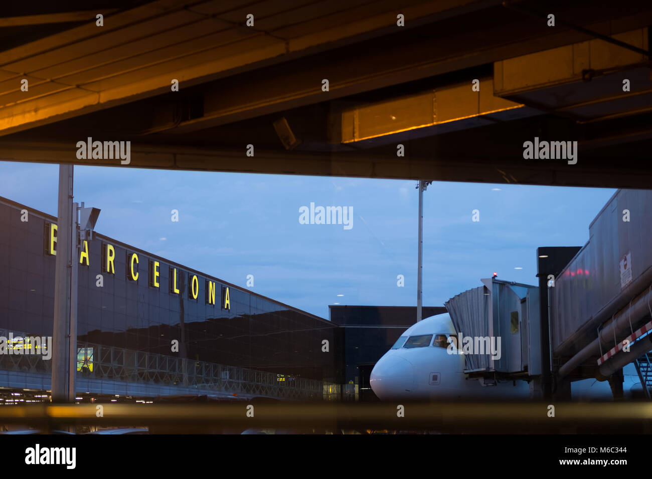 Barcelona, Spain - September 25, 2017; Glass facade and airplane as seen through the boarding area of Barcelona - Stock Image