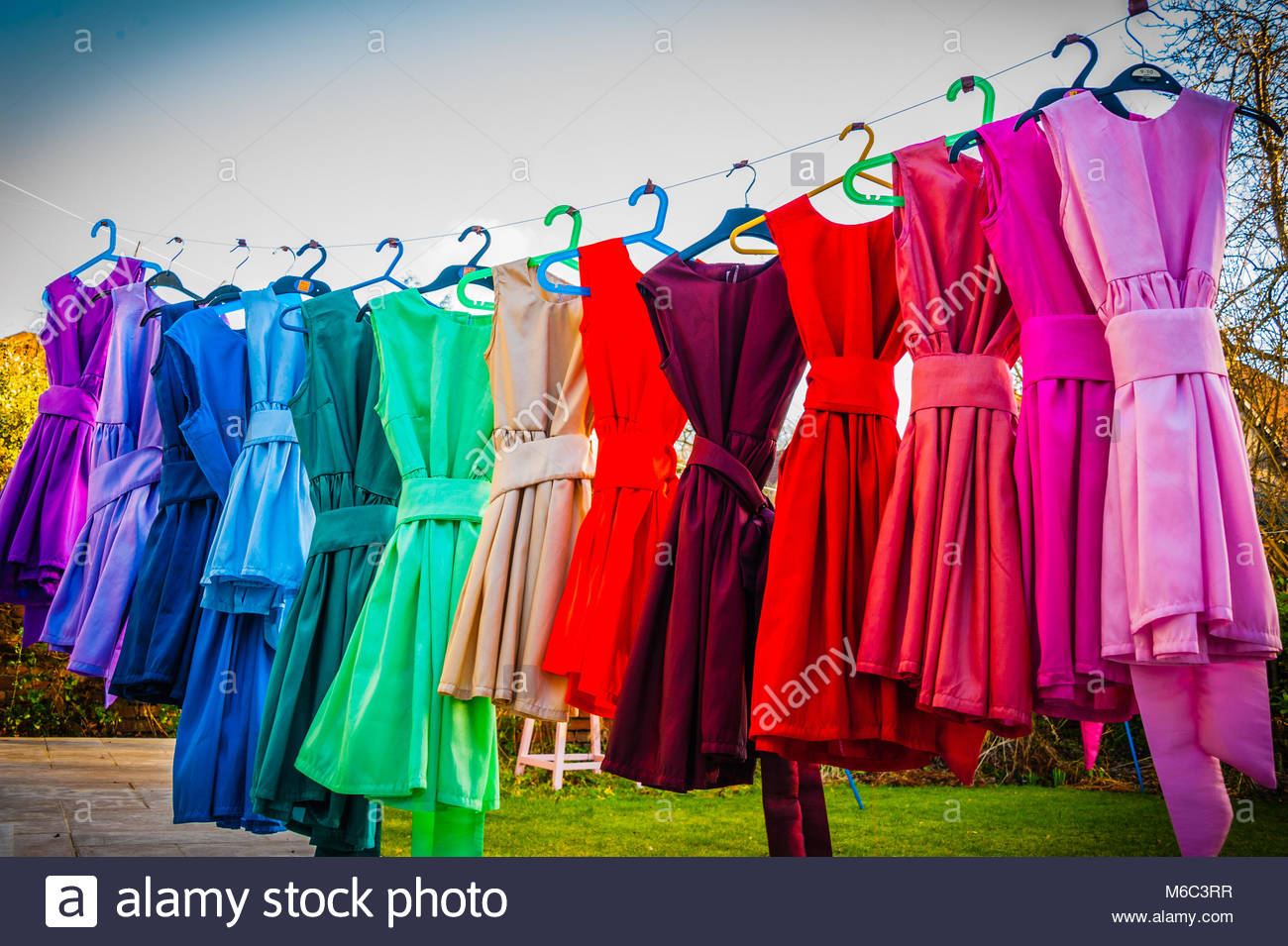 Children's Colourful dance dresses on a washing line in the late afternoon winter sun. 14 Rainbow coloured hand Stock Photo