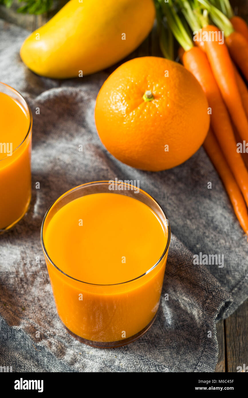 Healthy Organic Orange Carrot Smoothie Juice Drink with Mango and Banana - Stock Image