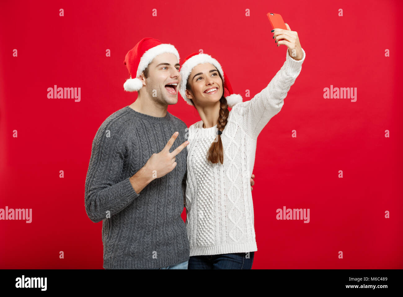 Christmas Concept - Young attractive couple taking a selfie by mobile phone celebrating in Christmas day - Stock Image