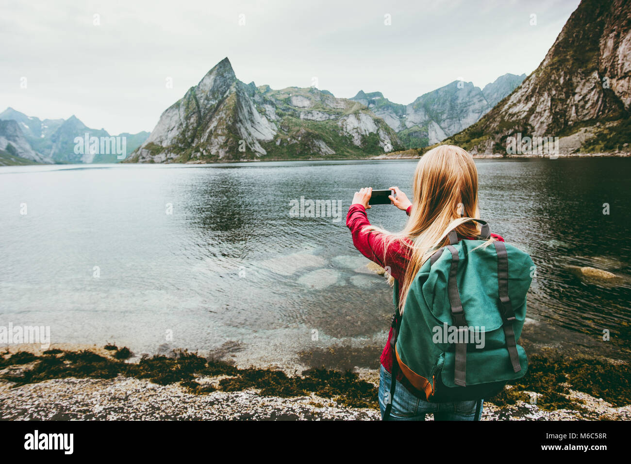 Girl tourist taking photo by smartphone sightseeing Lofoten islands Travel lifestyle wanderlust concept adventure - Stock Image
