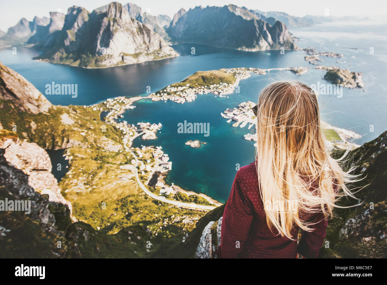 Blonde woman on the top of Reinebringen mountain fjord aerial view in Lofoten islands of Norway Travel backpacking - Stock Image