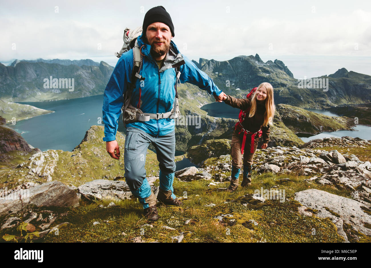 Happy Couple hiking in Norway mountains love and travel holding hands man and woman together Lifestyle concept vacations - Stock Image