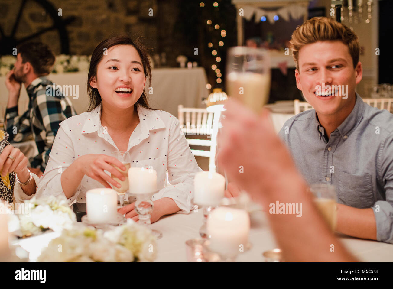 Wedding guests are socialising at the dinner party. Stock Photo