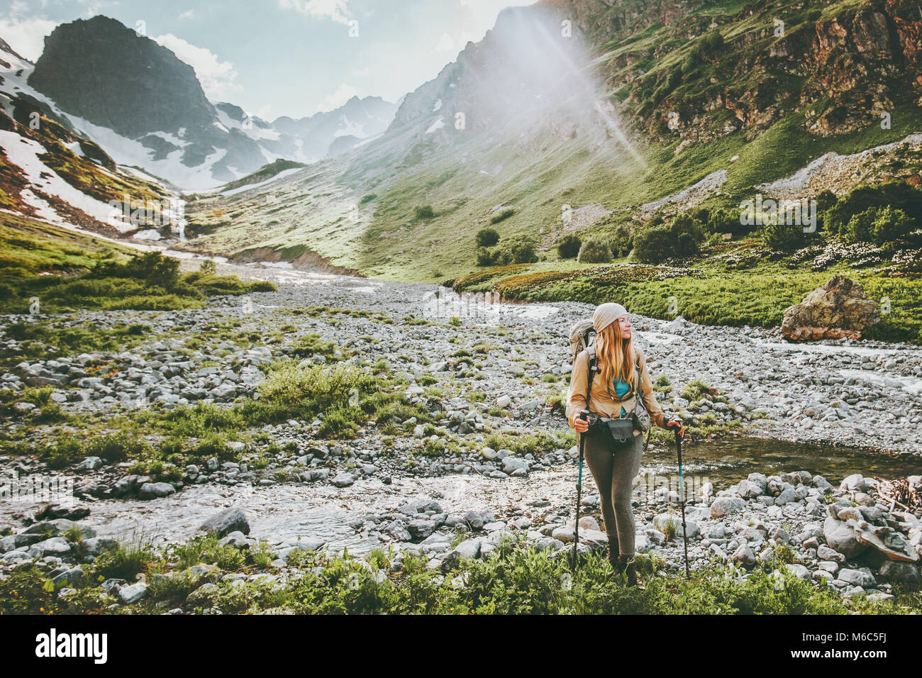 Woman backpacker hiking in mountains adventure travel lifestyle concept active summer vacations sport outdoor - Stock Image