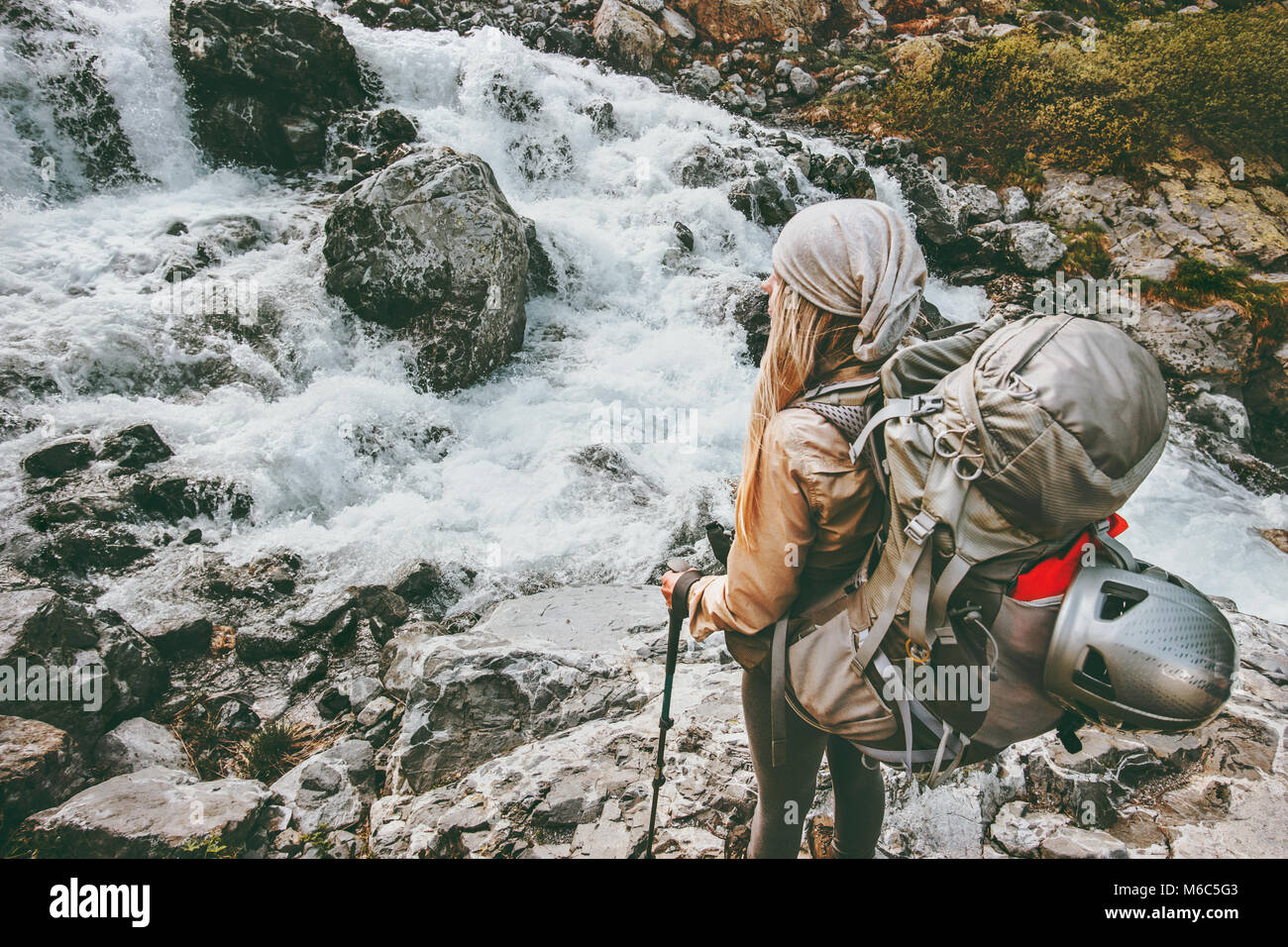 Adventurer travel woman hiking with backpack at river in mountains healthy lifestyle concept active summer vacations - Stock Image
