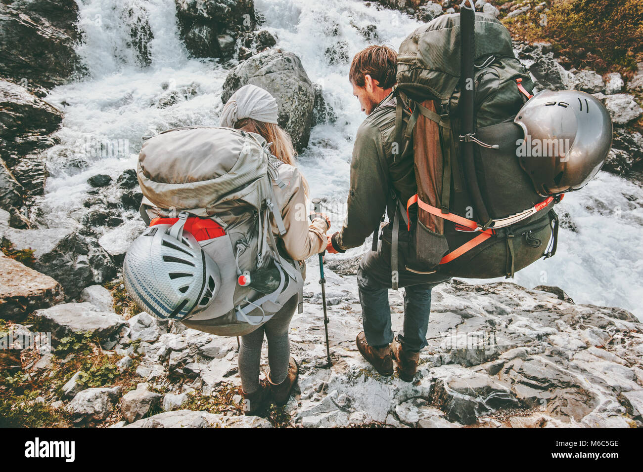 Couple backpackers friends hiking in mountains at river love and Travel Lifestyle wanderlust concept adventure vacations - Stock Image