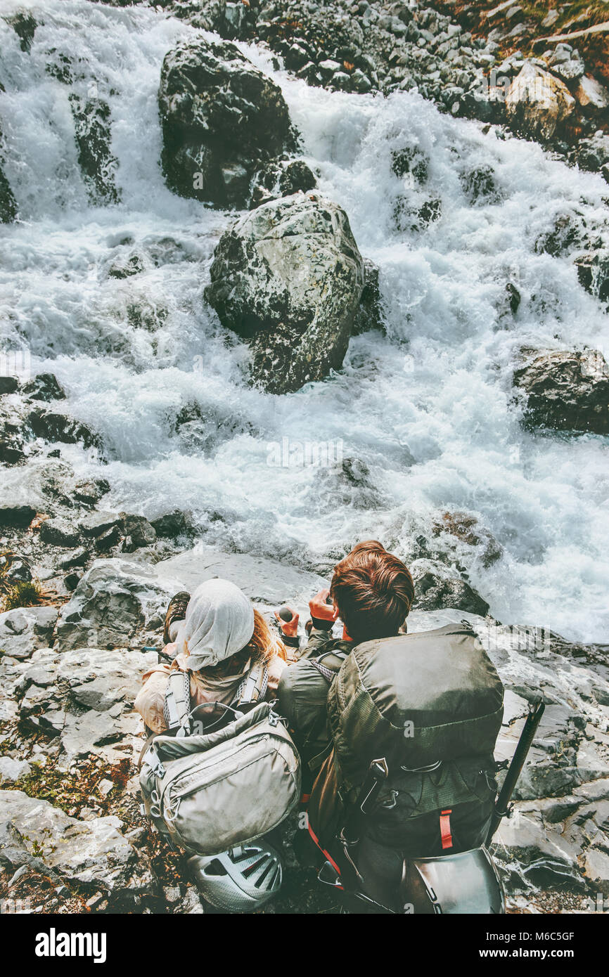 Couple adventurers relaxing at mountain river together love and Travel Lifestyle wanderlust concept adventure vacations - Stock Image