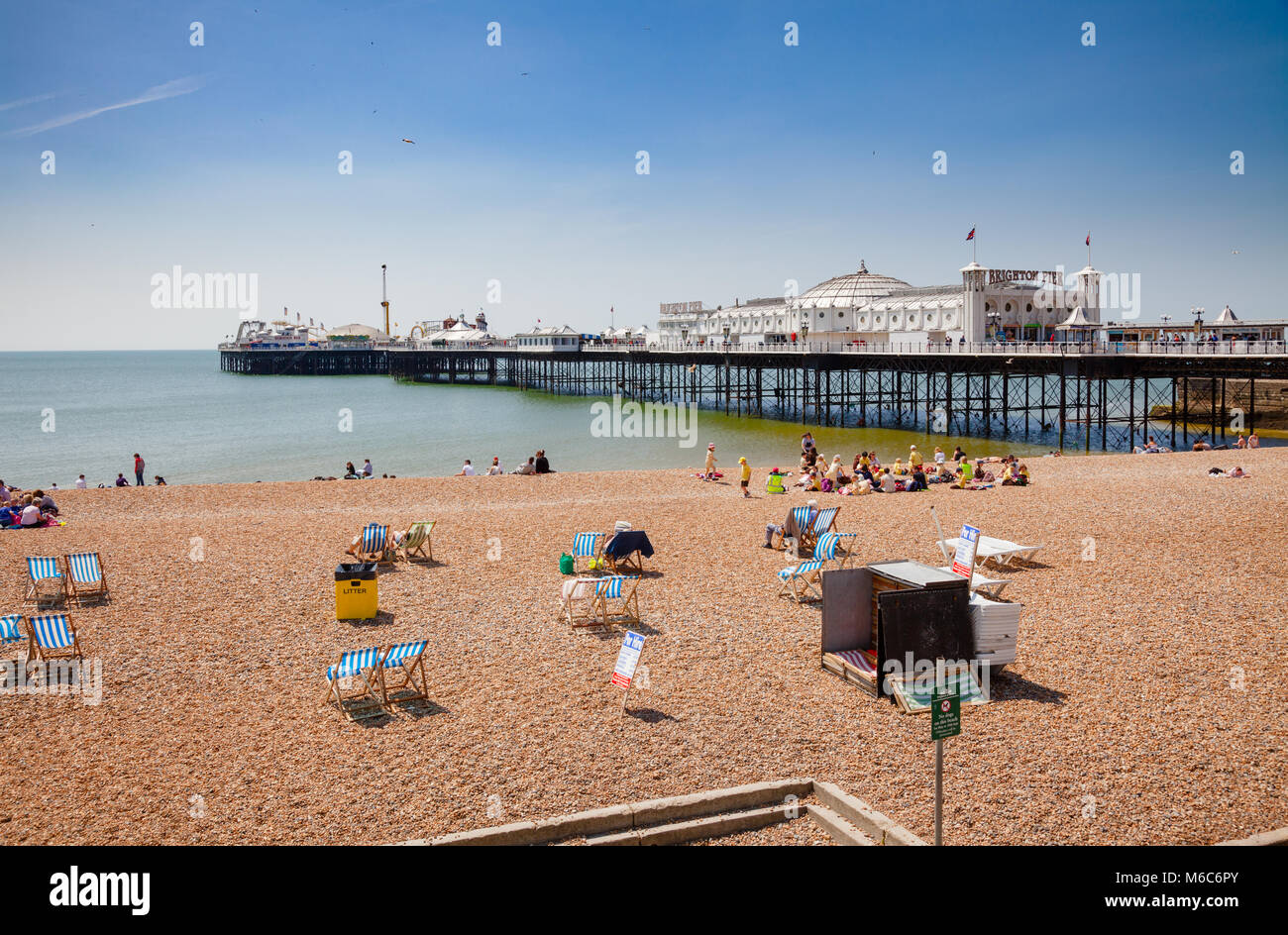 BRIGHTON, UK - JUN 5, 2013: Holidayers enjoying good summer weather at shingle beach near the Brighton Palace Pier - Stock Image