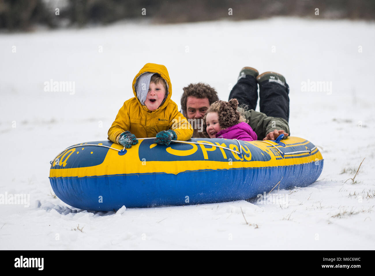 Phil Rogers and kids Rocco and Ruby sledge using an inflatable dinghy in Batheaston in Somerset after heavy snowfall. - Stock Image