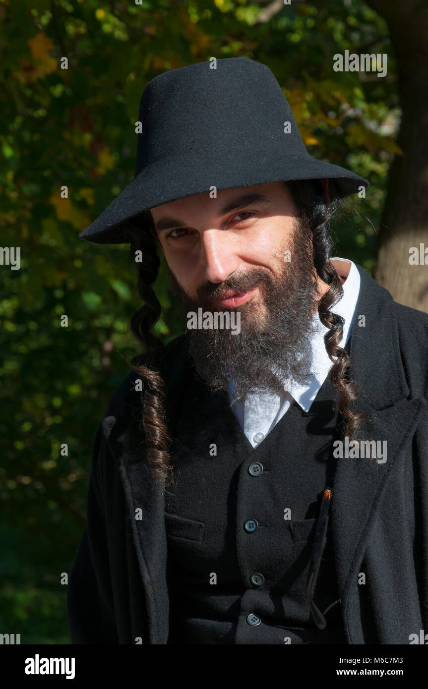 Jewish orthodox man with black beard, hat, white shirt, jerkin and coat outdoors. What is Judaism and how real Jewish - Stock Image