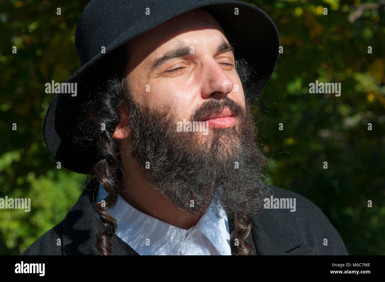 e331f566bb5 Outdoor sunny bright portrait of a young traditional orthodox Jewish man  with eyes closed with black