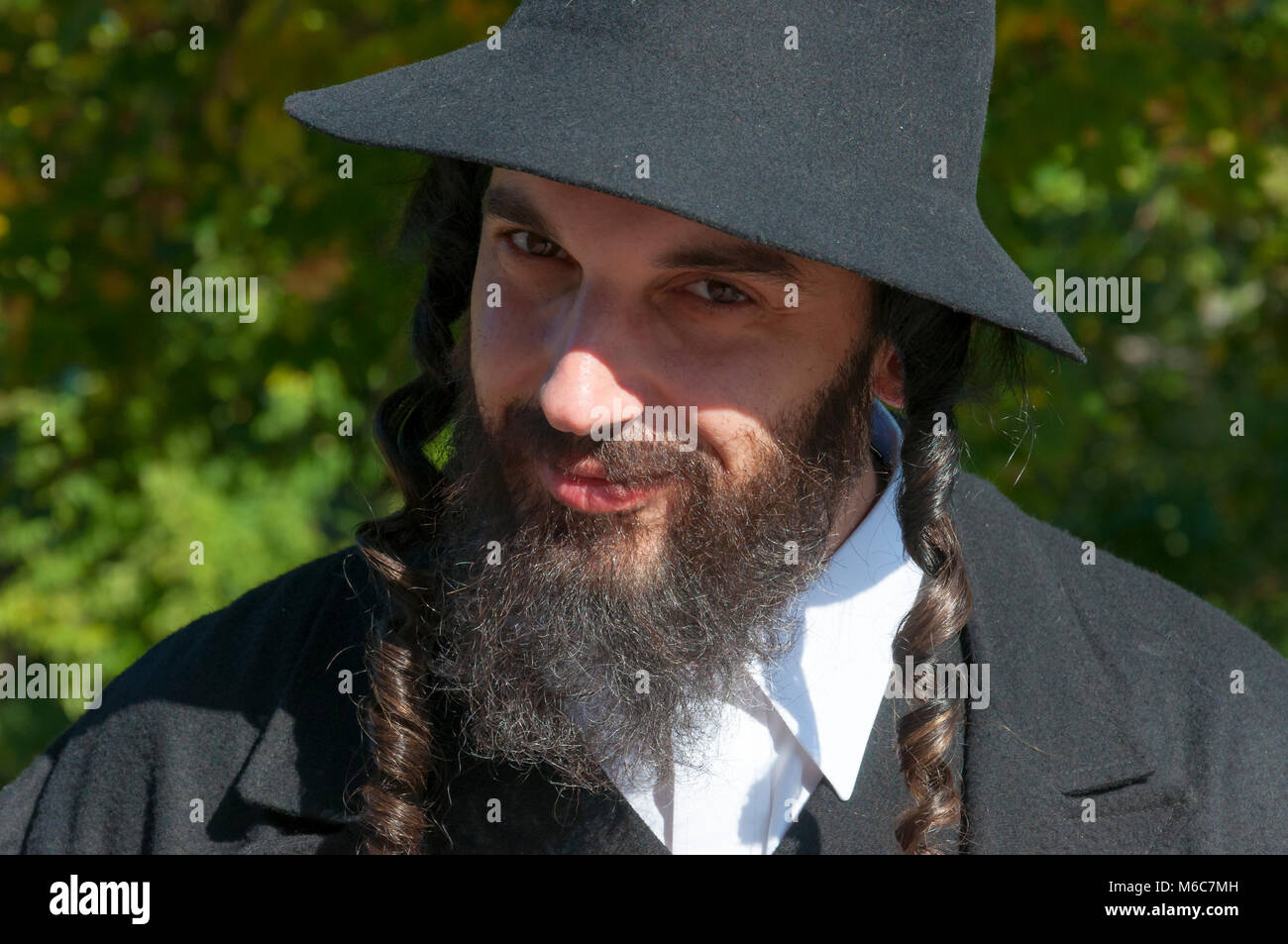 b1a505ff41e Outdoor sunny portrait of a smiling looking young orthodox Jewish man with black  beard and hat