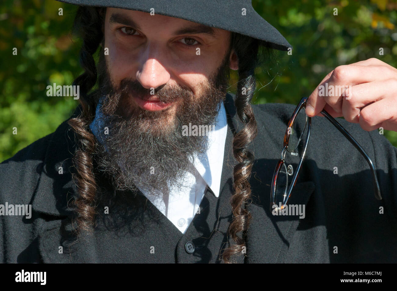 dbdab0918db Outdoor sunny bright portrait of a smiling young traditional orthodox  Jewish man with black beard