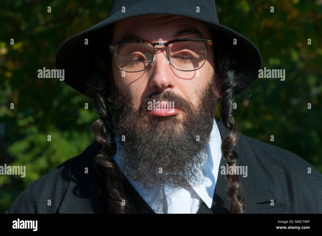 303f968fec8 Outdoor sunny portrait of bewildered closed eyes young traditional orthodox  Jewish man with black beard and