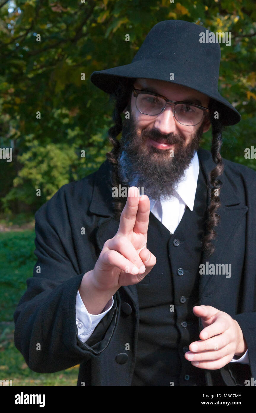 43beaea164f Sunny outdoor portrait of a young smiling happy fingers blessing  traditional orthodox Jewish man with black
