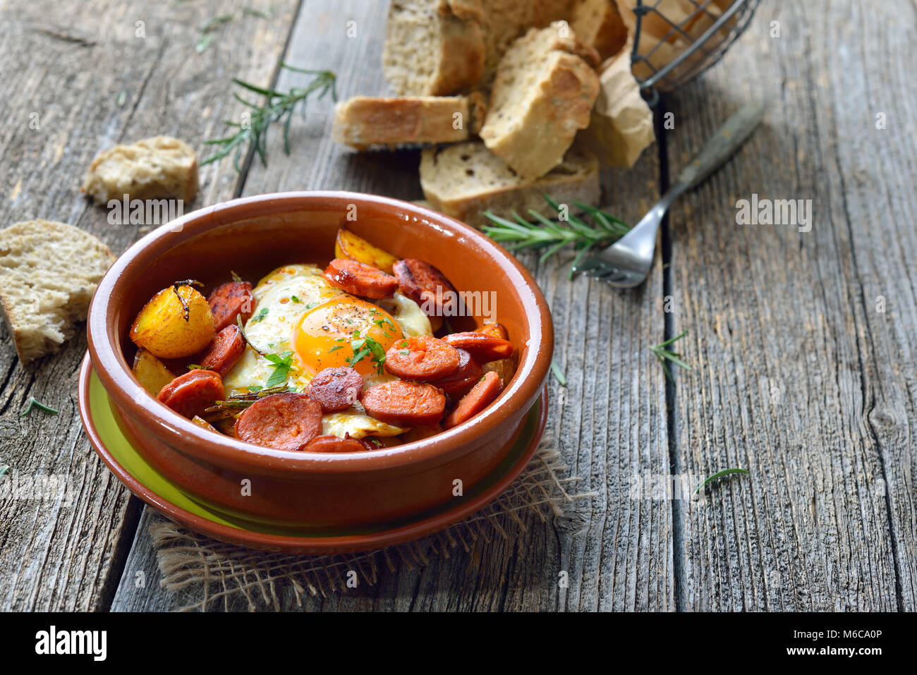 Spanish tapa: Spicy chorizo sausage with fried egg and baby potatoes served in a terra cotta cazuela dish Stock Photo