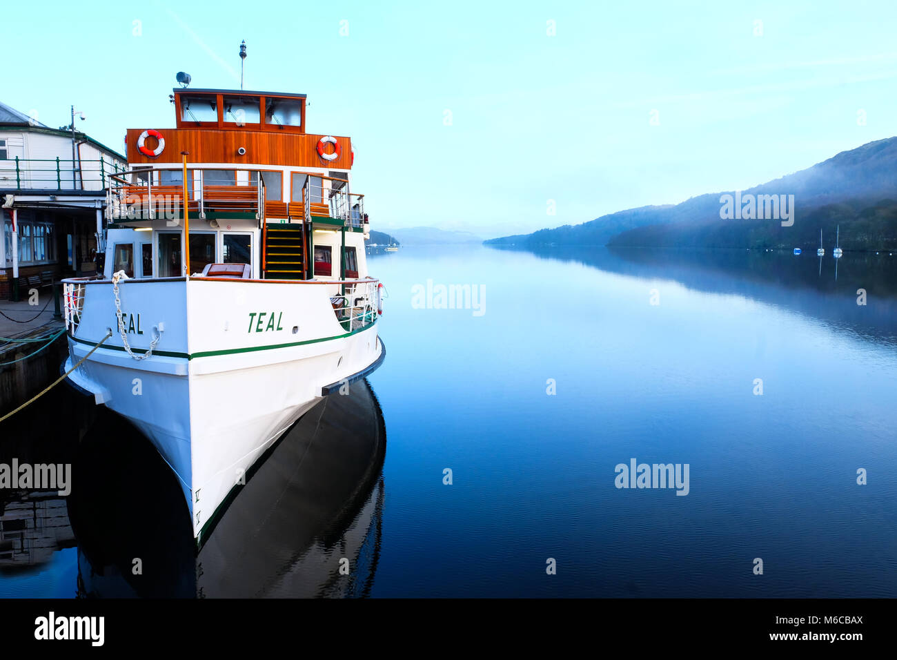 white and wooden vintage Steam ferry moored on lake Windermere, Lake District, UK, early morning view across the - Stock Image