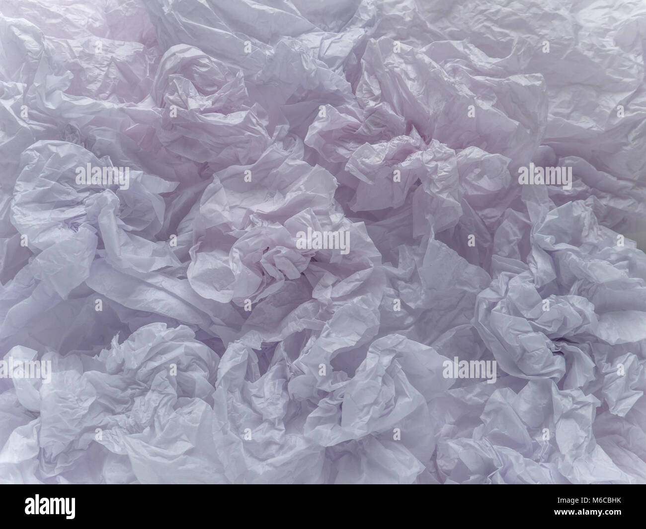 Crumpled pale pinkish violet packing paper sheets background - Stock Image