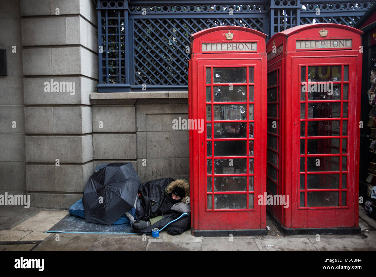 Rough sleeper, homeless man sleeping next to red telephone boxes on Piccadilly, central London, UK - Stock Image