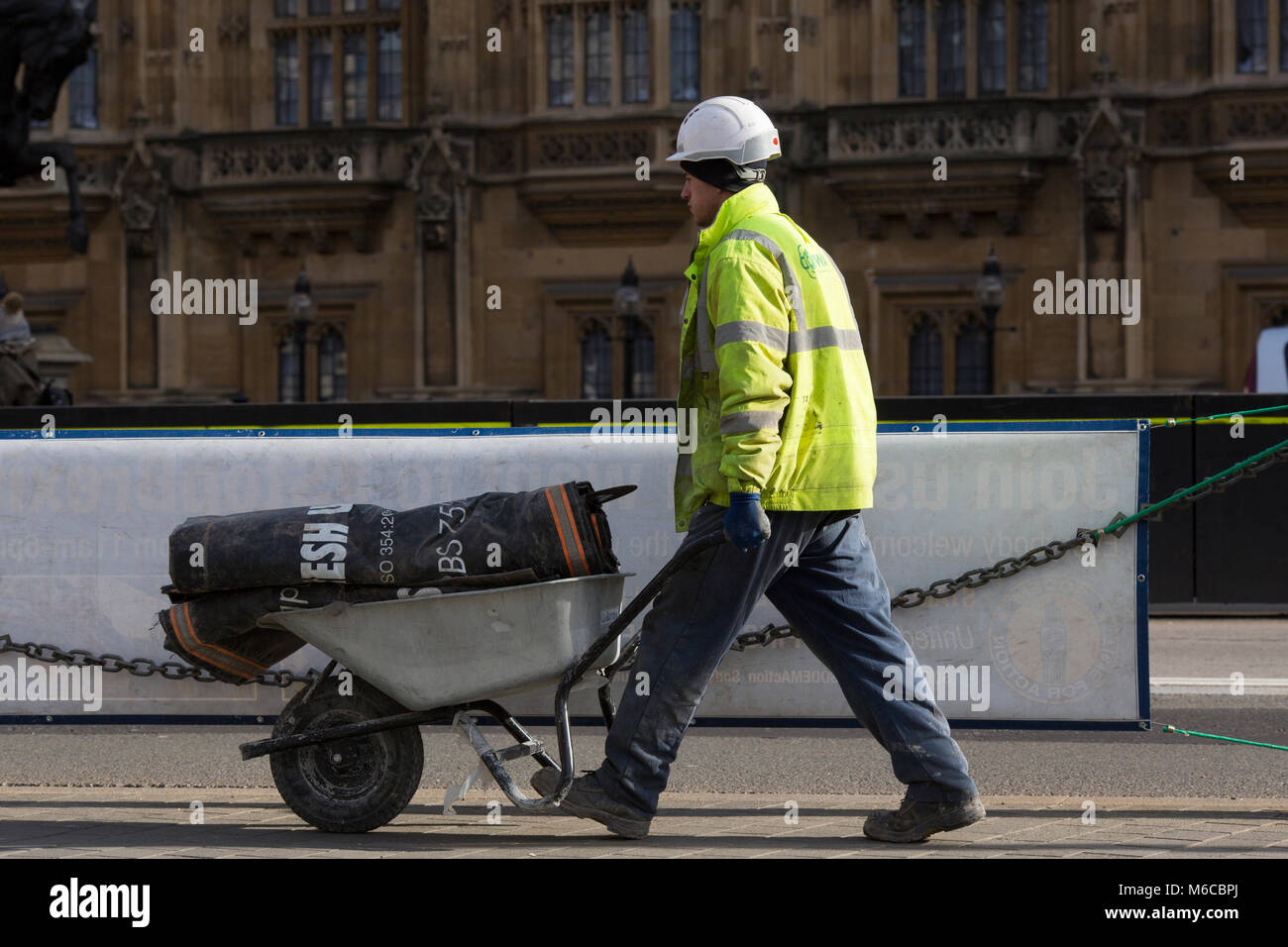 A construction worker wheels materials towards renovated parts of the Houses of Parliament, Whitehall, London, United Stock Photo