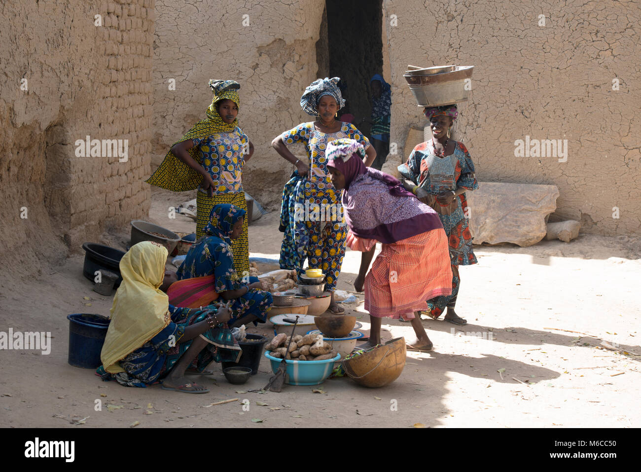 Indigenous, ethnic Fulani women in traditional, bright colourful dress selling food at a small village market in - Stock Image