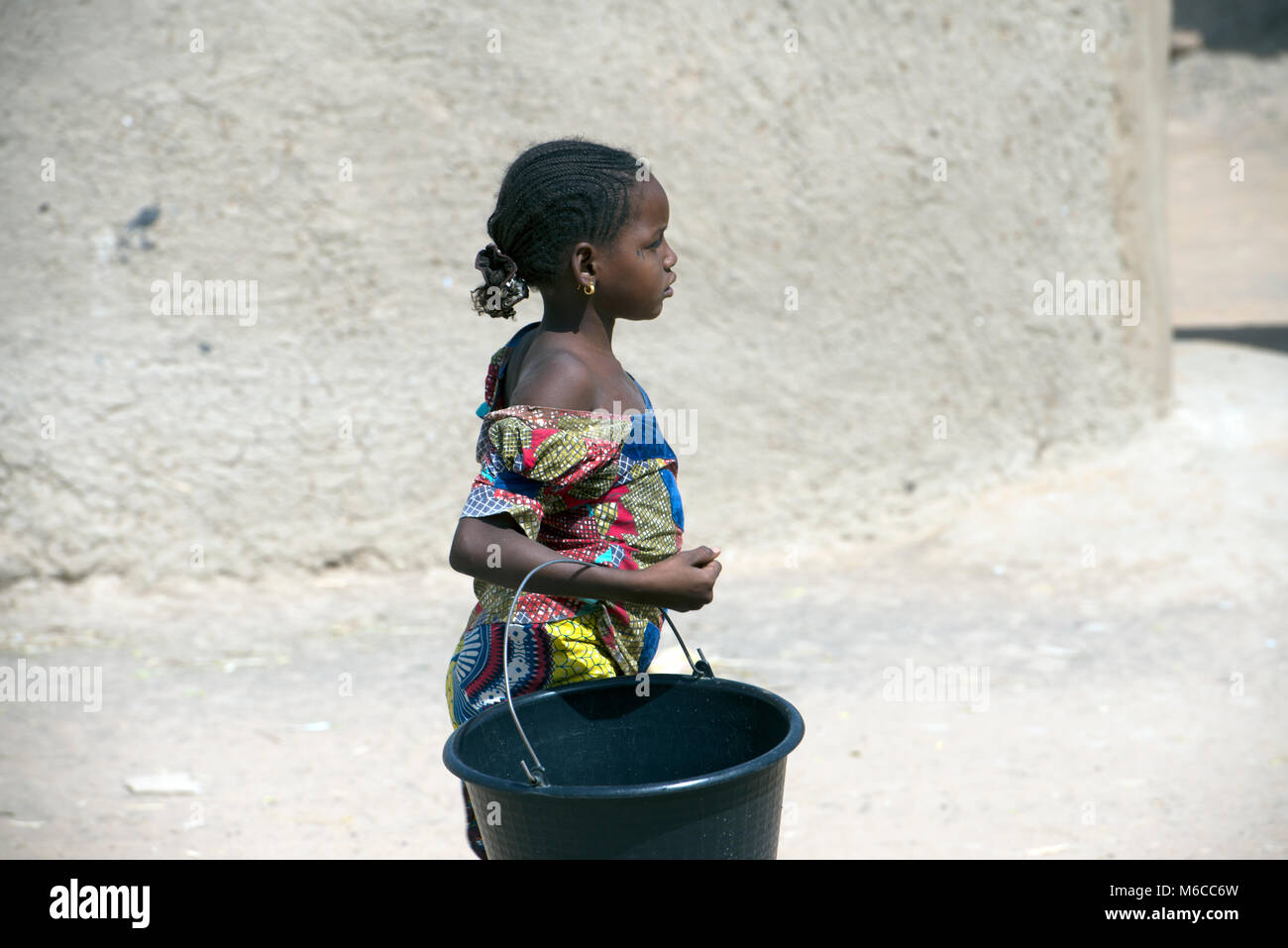A young indigenous ethnic Fulani girl walking through her village carrying a bucket of water. Mali, West Africa. - Stock Image
