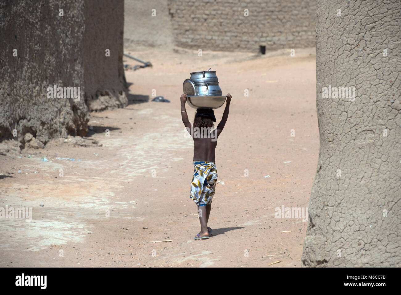 A young, ethnic, indigenous Fulani girl walking in her village while carrying pots on her head. Mali, West Africa. - Stock Image