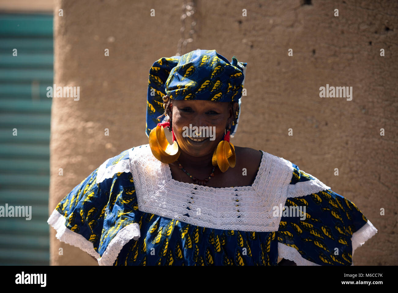 An indigenous, ethnic Fulani woman who makes earrings for a living. Mali, West Africa. - Stock Image