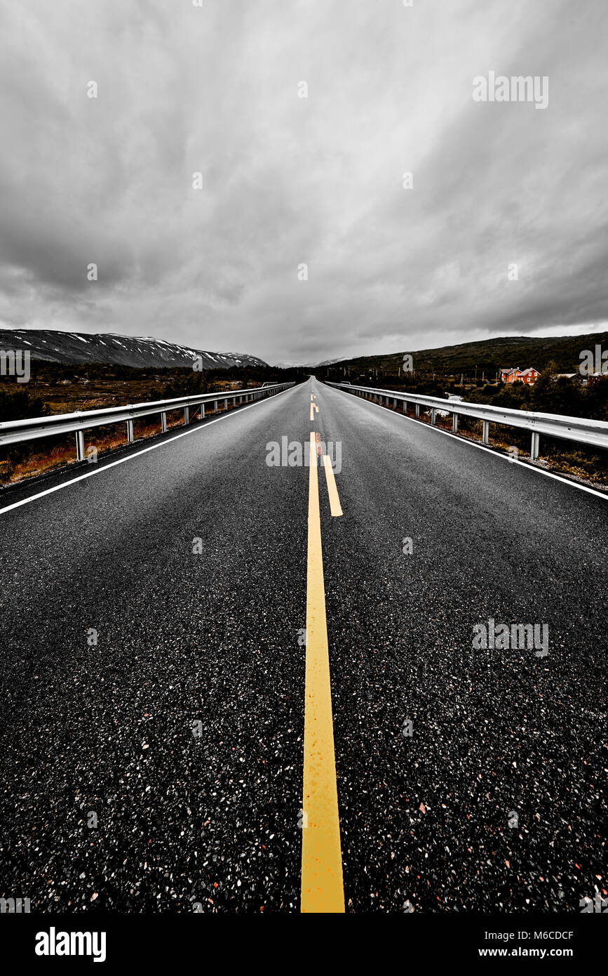 image of a wide open prairie and mountains with a paved highway road stretching out as far as the eye can see with beautiful nature under a cloudy sky Stock Photo