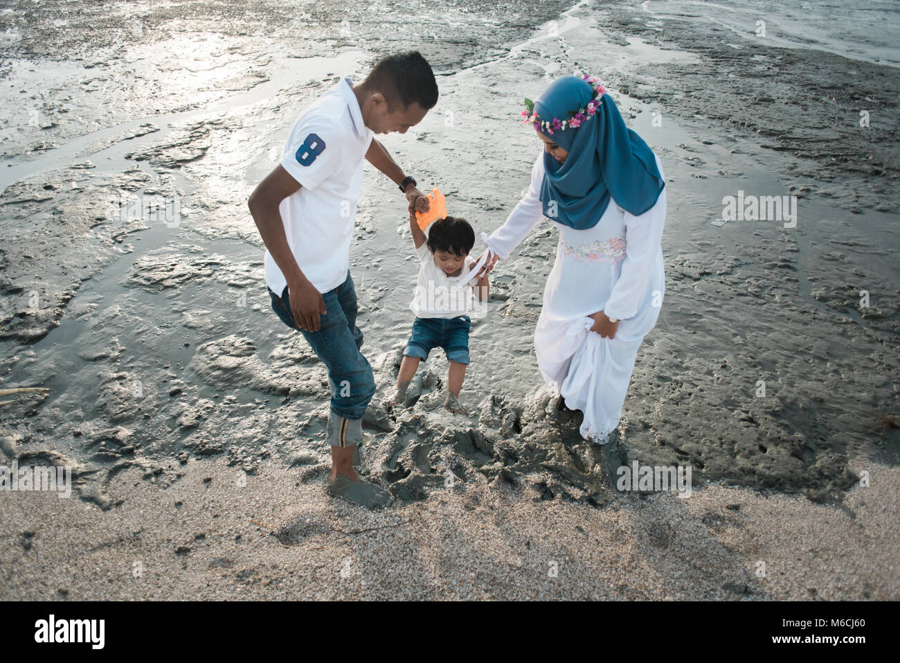 happy asian family wearing casual and playing with mud at the muddy beach located in pantai remis, kuala selangor, - Stock Image