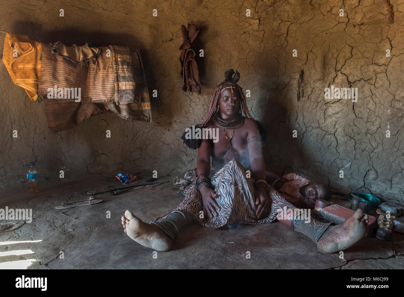 Woman of the Ovahimba or Himba people cleaning and disinfecting clothes and body, Kunene district, Namibia - Stock Image