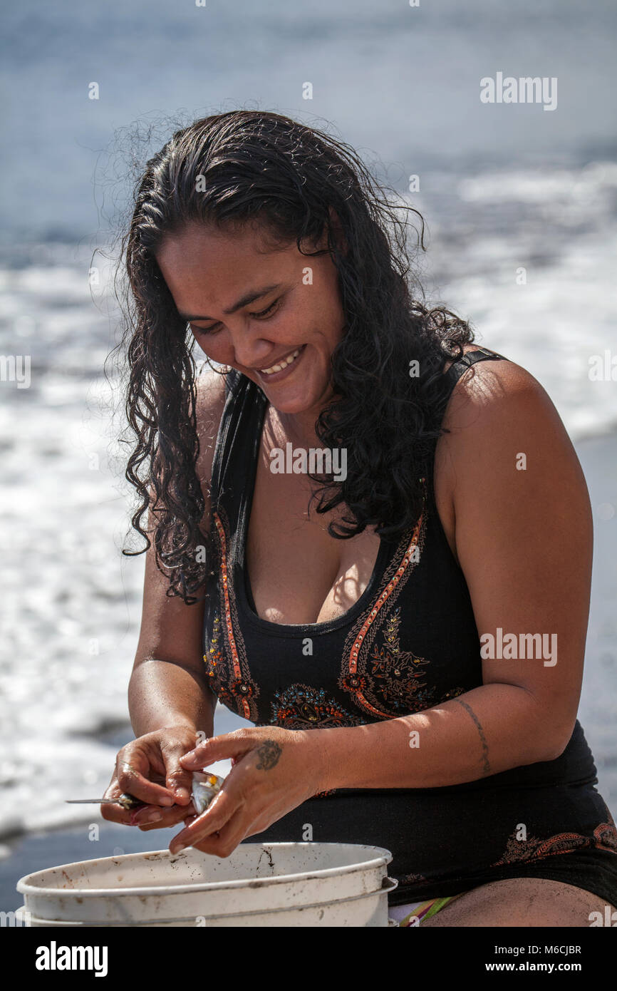 Woman, Polynesian, laughs, cleans fish on the beach, swimsuit, Tahiti, French Polynesia - Stock Image