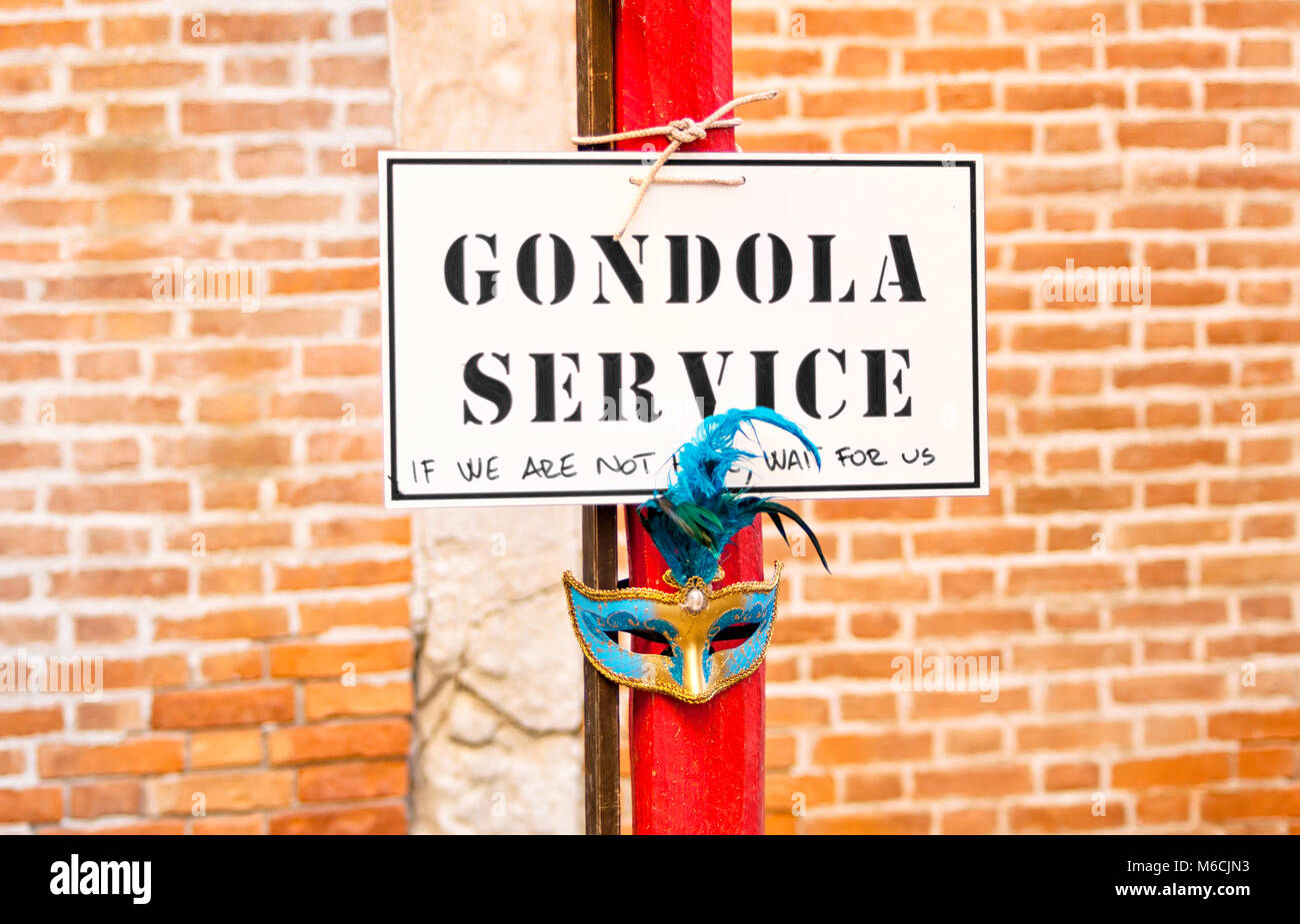 Detail of a Gondola service sign over a red pole in the Venice lagoon. The Gondola s a traditional flat-bottomed - Stock Image