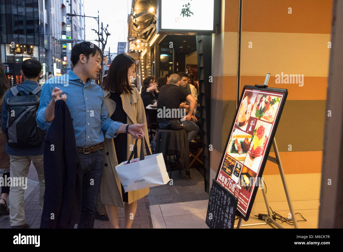 Couple walking check a restaurant menu in Ginza, Tokyo, Japan - Stock Image