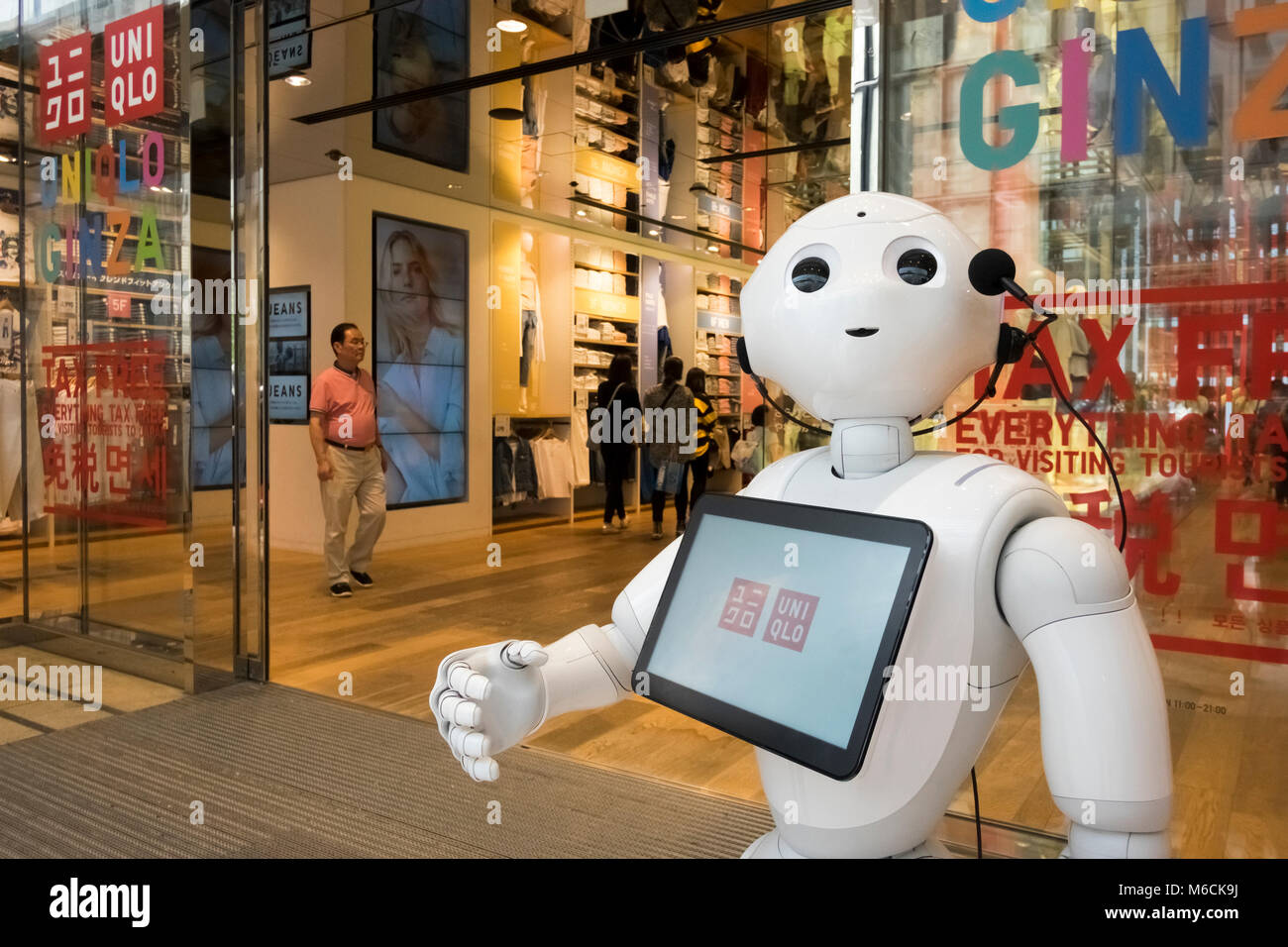 A robot welcomes shoppers to the flagship Uniqlo store in Ginza, Tokyo, Japan - Stock Image