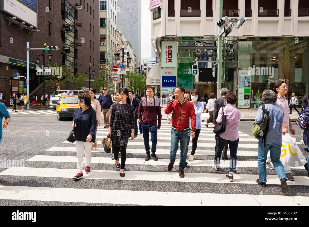 People on a pedestrian crossing in the Ginza district of Tokyo city, Japan - Stock Image