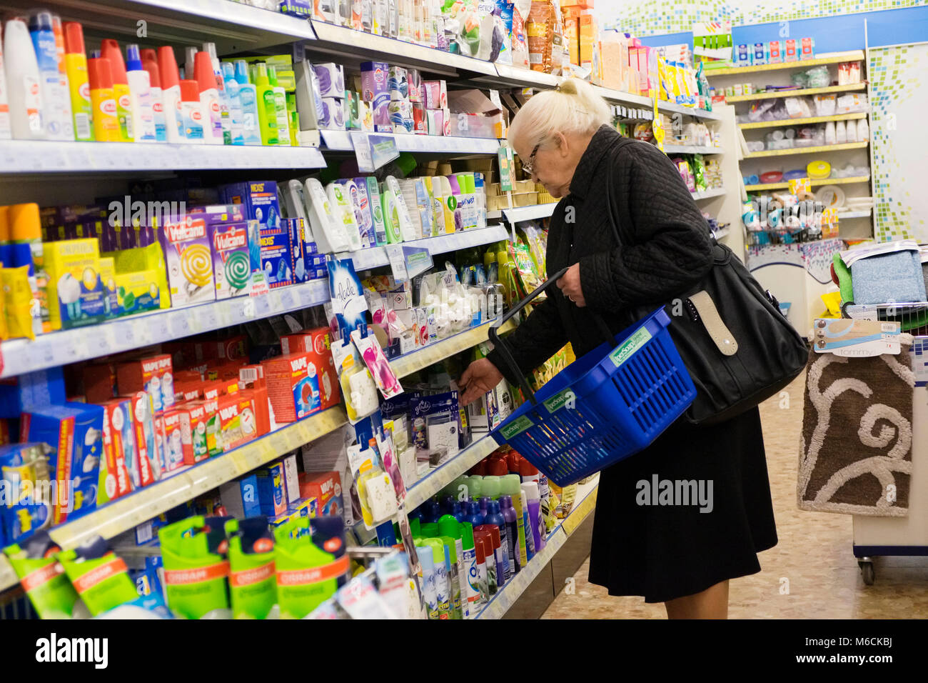 An elderly lady shopping in a drug store chemist shop - Stock Image