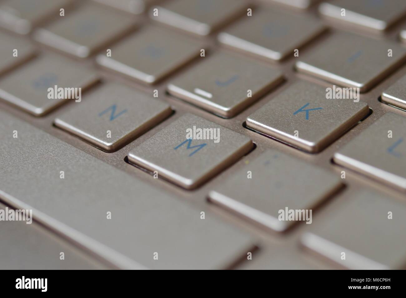 Keyboard of a bronze colored laptop - Stock Image