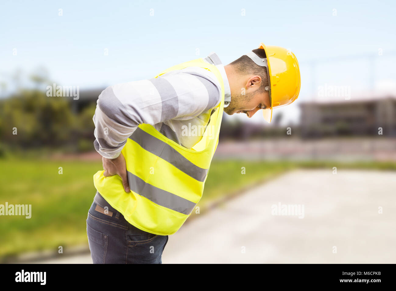 Construction worker feeling backpain in lumbar area pressing painful lower back and leaning forward - Stock Image